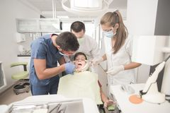 Boy with perfect teeth scared at the dentist. Scared teenager boy is having a check up at the dentist Royalty Free Stock Photos