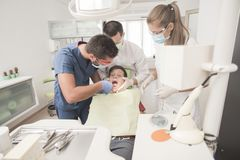 Boy with perfect teeth scared at the dentist. Scared teenager boy is having a check up at the dentist Stock Photo