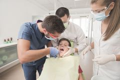 Boy with perfect teeth scared at the dentist. Scared teenager boy is having a check up at the dentist while dentist takes out a tooth Stock Images