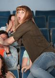 Scared Woman. Scared young Caucasian women jumps out of her seat in theater Royalty Free Stock Photo