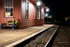 Scared woman alone at the train station. A woman sits on a train station bench, scared and cold stock photography
