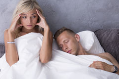 Scared woman in bed with lover. Scared naked women sitting in bed while her lover is still sleeping