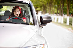 Scared woman behind the wheel. Young woman stopping the car and screaming Stock Images
