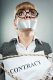 Scared woman bound by contract with taped mouth. Royalty Free Stock Images