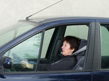 Scared woman in car. Woman driving car and has scared look royalty free stock image