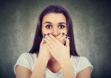 Scared woman covers her mouth to keep it quiet. On gray background royalty free stock image