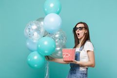 Scared woman in 3d glasses watching movie film, hold bucket of popcorn celebrating with colorful air balloons isolated stock photos