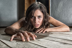 Scared woman on the floor. Scared woman crawling on the floor of a derelict house royalty free stock images
