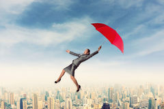 Scared woman flying in the sky with umbrella Royalty Free Stock Image