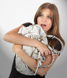 Scared woman handbag robbery. Portrait of a scared young attractive woman clenching to her handbag afraid of an imminent robbery or mugging in street crime Royalty Free Stock Photos