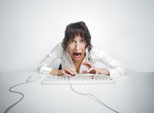 Scared woman at her office desk Royalty Free Stock Image