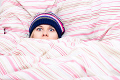 Scared woman hiding in duvet. Scared woman in winter hat hiding wrapped in duvet Stock Photos