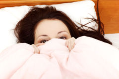 Scared woman hiding her face under the sheet. Royalty Free Stock Photo
