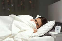 Scared woman hiding under blanket on a bed in the night Stock Photos