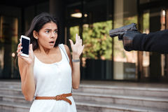 Scared woman holding cell phone threatened by criminal with gun Stock Photo