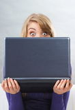 Scared woman holding laptop and looking out from behind computer Stock Photo