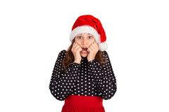 Scared woman looks nervously, biting fingernails and afraid of something. emotional girl in santa claus christmas hat isolated on. White background. holiday stock image