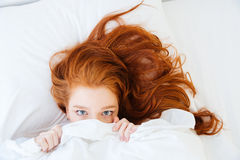 Scared woman lying in bed and hiding under the sheet Royalty Free Stock Image