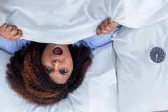 Scared woman lying in bed stock photo