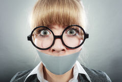 Scared woman with mouth taped shut. Censorship. Royalty Free Stock Photos