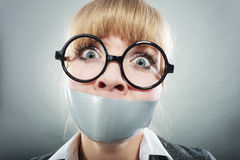 Scared woman with mouth taped shut. Censorship. Stock Image
