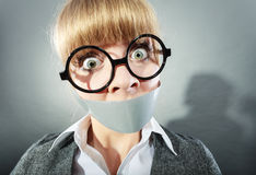 Scared woman with mouth taped shut. Censorship. Royalty Free Stock Images