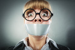 Scared woman with mouth taped shut. Censorship. Royalty Free Stock Photography