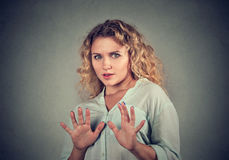 Scared woman raising hands up in defense. Afraid about to be attacked or avoiding unpleasant situation, isolated on gray background. Negative human emotion Stock Photos