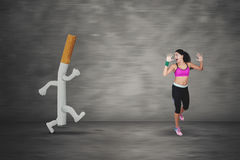 Scared woman running away by a cigarette Stock Images