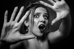 Scared woman screaming. Fun stressed scared girl in dark looking at camera screaming, monochrome Stock Image