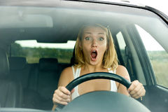 Scared woman shouts driving the car. Outdoors stock photo