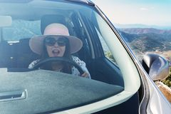 Scared woman shouts while driving the car. Outdoors stock photography