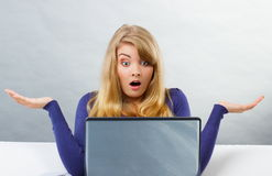 Scared woman shrugging shoulders and looking at laptop, computer problem Royalty Free Stock Photography