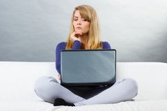 Scared woman sitting on sofa and looking at laptop, modern technology Stock Images