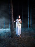 Scared woman walking in foggy night forest with lantern Stock Images