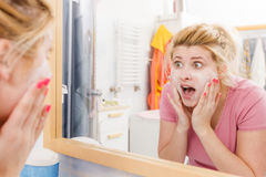 Scared woman washing her face under sink. Sensitive, dry skin problems concept. Scared woman washing her face under sink Royalty Free Stock Image