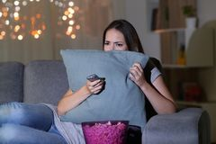 Scared woman watching terror movie in the night. Sitting on a couch in the living room at home Royalty Free Stock Photography