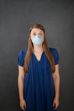 Scared woman wearing surgical mask Stock Photo