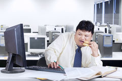Scared worker using computer in office. Male worker looks scared when looking at a monitor in the office while eating a burger Stock Photos