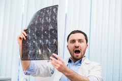 Scared worried doctor reviewing X-ray scan looking at the camera Indoors in office Royalty Free Stock Image