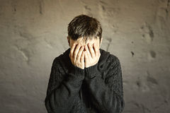 Scared and worried woman covering ger face with hands. Stock Photo