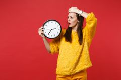 Scared worried woman in yellow fur sweater putting hand on forehead holding round clock isolated on red background. Time. Is running out. People sincere royalty free stock photos