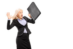 Scared young businesswoman protecting with briefcase and gesturi Royalty Free Stock Photo
