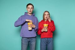 Scared young couple in casual clothes eating popcorn royalty free stock photography