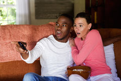 Scared young couple watching tv Stock Photos