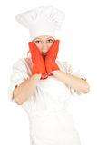 Scared young female cook with red kitchen gloves Royalty Free Stock Photo