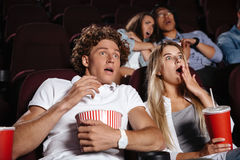 Scared young friends sitting in cinema watch film. Picture of scared young friends sitting in cinema watch film drinking aerated sweet water stock photography