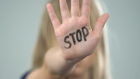 Scared young girl showing stop sign, domestic violence victim, abuse awareness