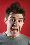 Scared young man. Headshot of a scared young man against red background Stock Photos