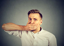 Scared young man covering mouth with hand Royalty Free Stock Photos